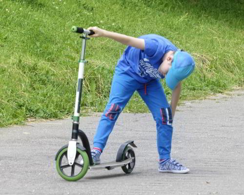Sommer: Junge mit Tretroller